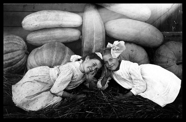 Two girls with pumpkins, squash, and watermelons