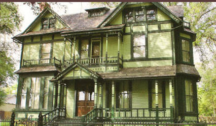 The exterior of an old, light green colored house with dark green trim. The house is 2-stories and has a front porch.