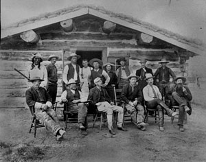 men sitting standing in front of cabin